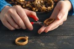 Fermez-vous de la main de femme filetant des perles sur le cordon pour faire le collier ou le bracelet artistique de perle Photos libres de droits