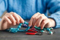 Fermez-vous de la main de femme filetant des perles sur le cordon pour faire le collier ou le bracelet artistique de perle Photographie stock