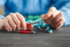 Fermez-vous de la main de femme filetant des perles sur le cordon pour faire le collier ou le bracelet artistique de perle image libre de droits