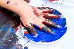 Fermez-vous de la main infantile imbibée en peinture bleue Image libre de droits