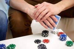 Fermez-vous de la main masculine avec jouer des cartes et des puces Photographie stock libre de droits