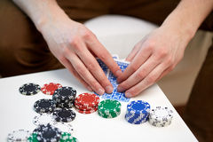 Fermez-vous de la main masculine avec jouer des cartes et des puces Image stock
