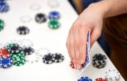 Fermez-vous de la main masculine avec jouer des cartes et des puces Image libre de droits