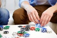 Fermez-vous de la main masculine avec jouer des cartes et des puces Photographie stock