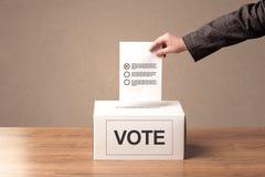 Fermez-vous de la main masculine mettant le vote dans une urne  Photo stock