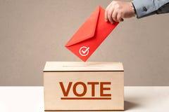 Fermez-vous de la main masculine mettant le vote dans une urne  Images stock