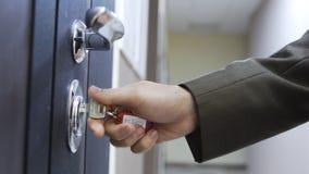 Fermez-vous de la main masculine ouvre la porte d'une maison avec la cl? photographie stock