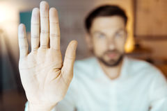 Fermez-vous de la main masculine qui étant sur le premier plan Images stock