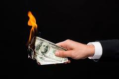 Fermez-vous de la main masculine tenant l'argent brûlant du dollar images libres de droits