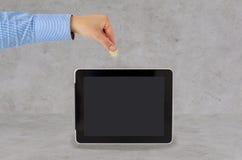 Fermez-vous de la main mettant la pièce de monnaie dans le PC de comprimé Photo stock