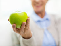 Fermez-vous de la main supérieure de femme tenant la pomme verte Photographie stock
