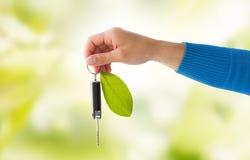 Fermez-vous de la main tenant la clé de voiture avec la feuille verte Images stock