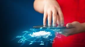 Fermez-vous de la main tenant le comprimé avec la technologie de réseau de nuage Photos libres de droits