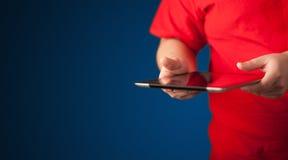 Fermez-vous de la main tenant le dispositif numérique de comprimé de touchpad Photographie stock libre de droits