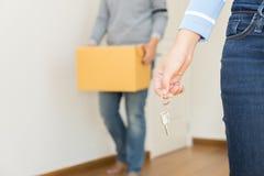 Fermez-vous de la main tenant une clé tandis qu'un homme tenant une boîte pour se déplacer Photographie stock libre de droits