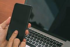 fermez-vous de la main utilisant le téléphone intelligent, ordinateur portable, paiement d'opérations bancaires en ligne photos libres de droits