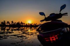 Fermez-vous de la moto et du coucher du soleil dans la campagne image stock