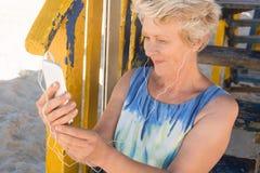 Fermez-vous de la musique de écoute de sourire de femme supérieure au téléphone intelligent image libre de droits