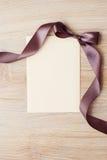 Fermez-vous de la note de carte avec le ruban brun sur le fond blanc Photo libre de droits