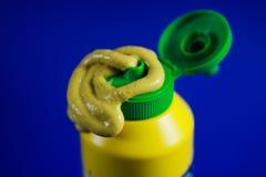 Fermez-vous de la pâte de la moutarde serrée une bouteille en plastique avec le fond bleu photo libre de droits