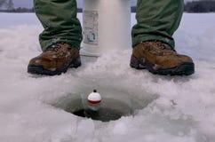 Fermez-vous de la pêche de pêcheur de glace en trou de glace photos stock
