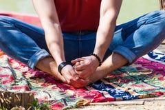 Fermez-vous de la partie inférieure du corps de jeune homme que le yoga de pratique extérieur par le lac étirant des hanches pose photos stock