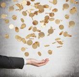 Fermez-vous de la paume ouverte et des pièces de monnaie d'or en baisse du dollar du plafond Photos stock