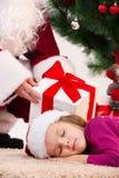 Fermez-vous de la petite fille de sommeil sous l'arbre de Noël. Photographie stock