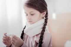 Fermez-vous de la petite fille pâle tenant le thermomètre image stock