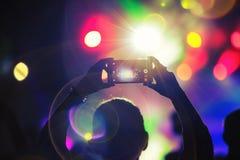 Fermez-vous de la photographie avec le smartphone pendant un concert Image libre de droits