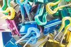 Fermez-vous de la pile des agrafes colorées de reliure Photographie stock