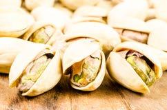 Fermez-vous de la pistache sur le fond en bois Image stock