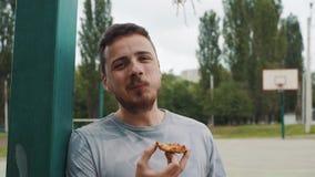 Fermez-vous de la pizza mangeuse d'hommes belle sur un terrain de basket clips vidéos