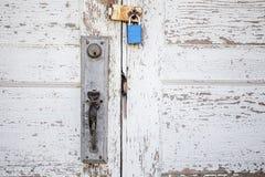 Fermez-vous de la porte blanche en bois superficielle par les agents padlocked Image libre de droits