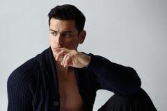 Fermez-vous de la pose belle de jeune homme sans chemise dans des vêtements noirs, sur le fond blanc Vue horizontale photo stock