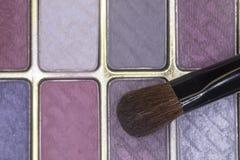 Fermez-vous de la poudre colorée de fard à paupières avec la brosse d'applicateur image libre de droits