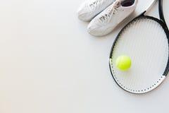 Fermez-vous de la raquette de tennis avec la boule et les espadrilles Images stock