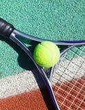 Fermez-vous de la raquette et de la boule de tennis sur le court de tennis Photographie stock