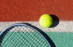 Fermez-vous de la raquette et de la boule de tennis sur le court de tennis Photographie stock libre de droits