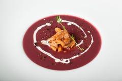 Fermez-vous de la soupe crème rouge avec le plat de calmar photographie stock libre de droits