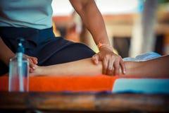 Fermez-vous de la station thermale de massage d'huile à la jambe à la main dans le jardin tropical pour le bien-être et le fond s image libre de droits