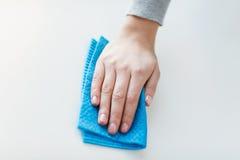 Fermez-vous de la surface de table de nettoyage de main avec le tissu Photographie stock