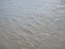 Fermez-vous de la surface sombre boueuse brune de rivière dans une zone rurale après forte pluie photographie stock