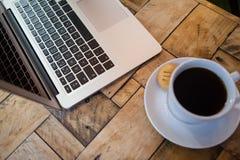 Fermez-vous de la tasse d'ordinateur portable et de café sur la table Photo libre de droits