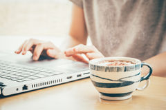 Fermez-vous de la tasse de café avec la femme de main employant le concept de labtop pour indépendant Photographie stock libre de droits