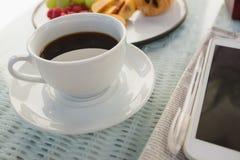 Fermez-vous de la tasse de café par le comprimé numérique sur la table Image stock