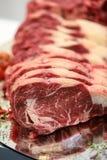 Fermez-vous de la viande crue sur la planche à découper Photos stock