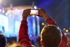 Fermez-vous de la vidéo d'enregistrement avec le smartphone pendant un concert Images libres de droits