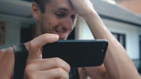 Fermez-vous de la vidéo de observation de sourire de jeune homme sur Smartphone extérieur au fond de cour ou de jardin clips vidéos