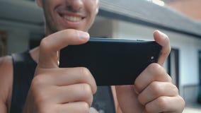 Fermez-vous de la vidéo de observation de sourire de jeune homme sur Smartphone extérieur au fond de cour ou de jardin banque de vidéos